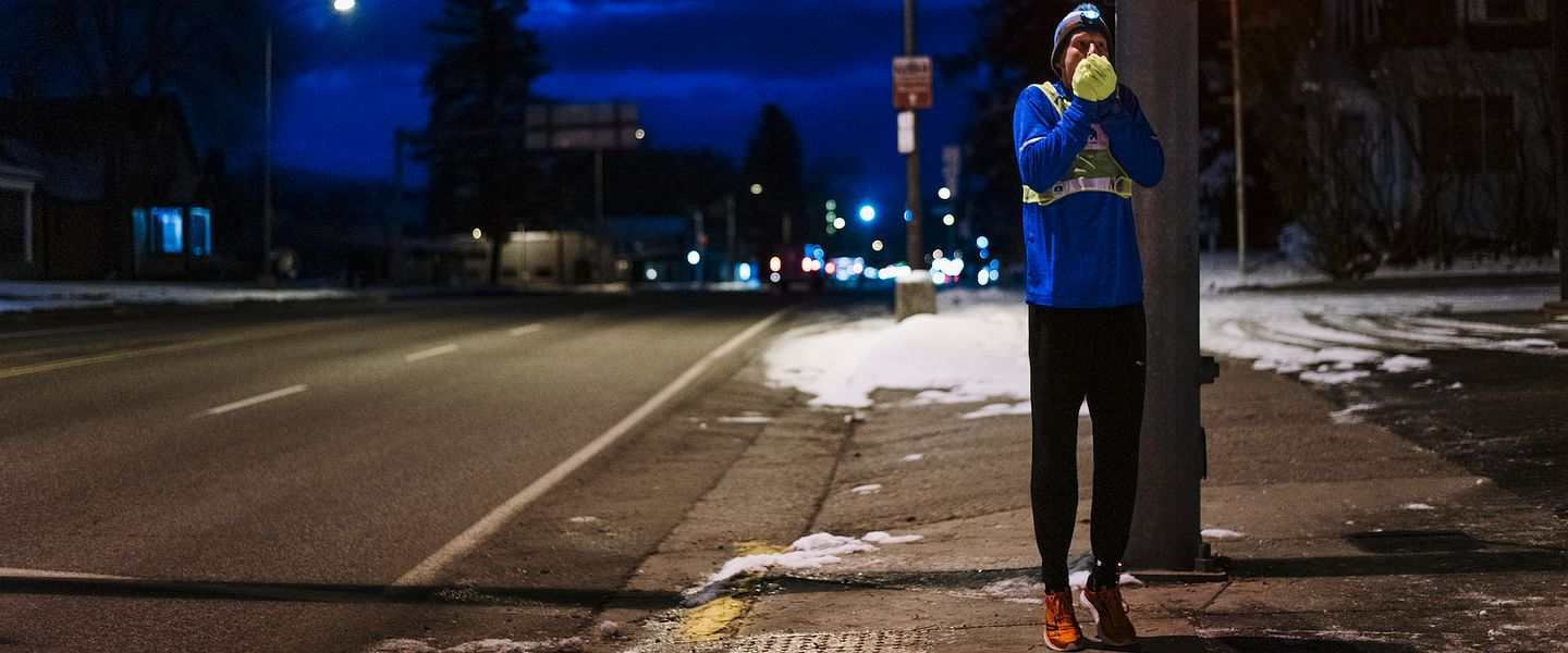 A runner warms his hands during an early morning run in the winter