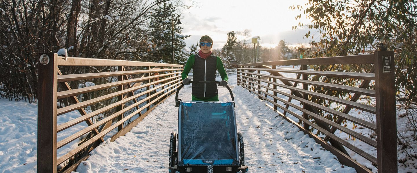 A runner pushes a stroller on a snow-covered sidewalk in winter