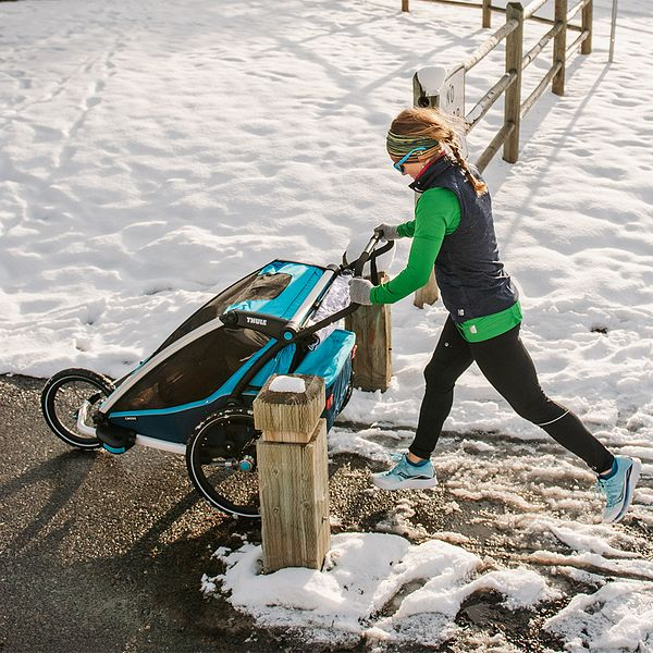 A woman wearing warm running clothes runs with a stroller during the winter