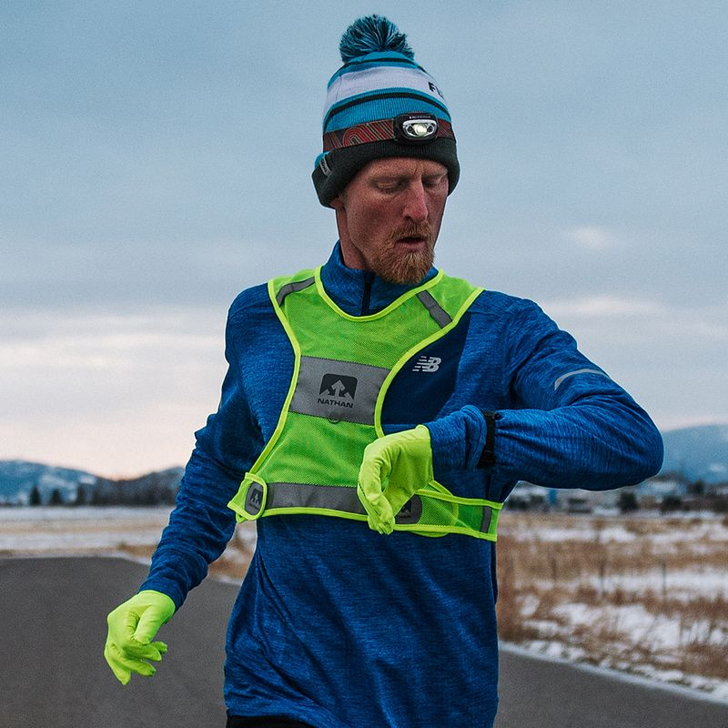 A man checks his GPS watch during a run in the winter