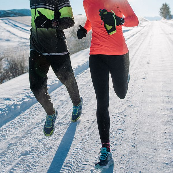 Two people running together on a snowy road during the winter