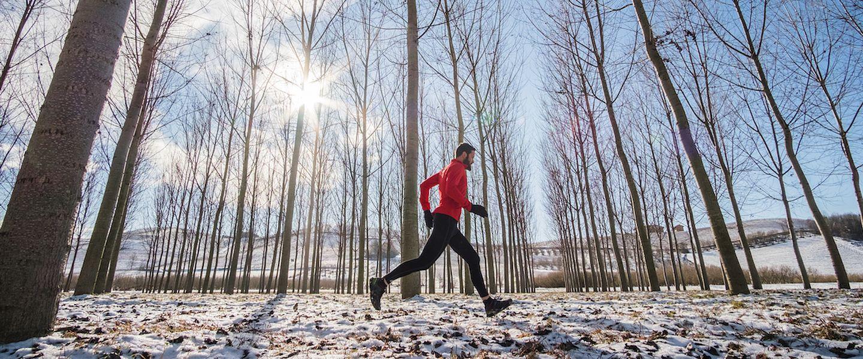 A man running through a snowy forest
