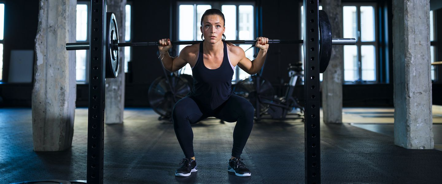 A runner does a squat with a barbell for strength training