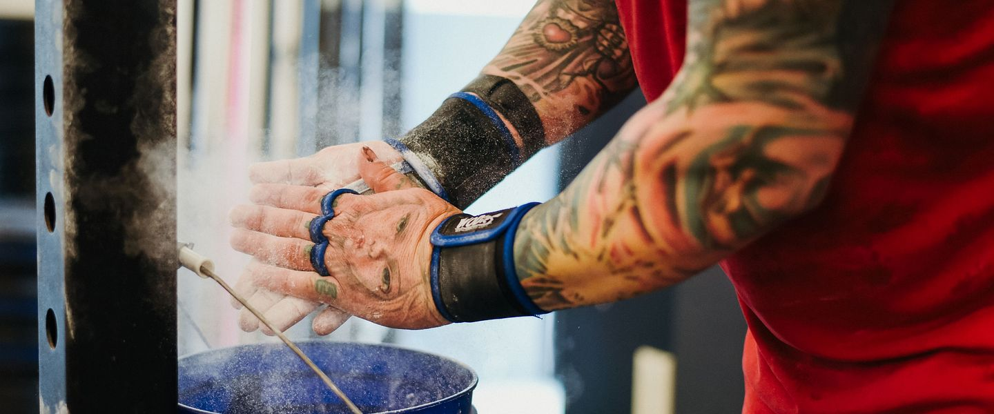 A man puts chalk on his hand before lifting weights in a gym