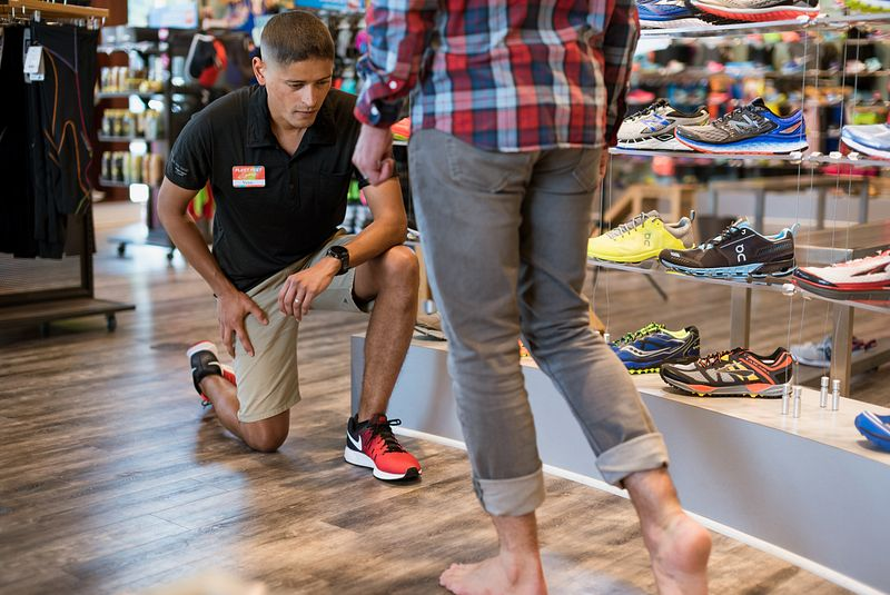 A Fleet Feet employee watches a customer walk to help find running shoes