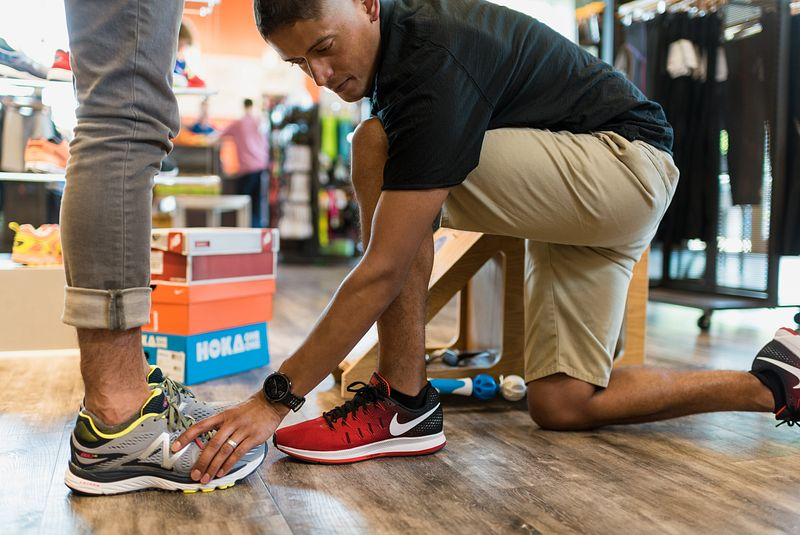 A Fleet Feet employee helps a customer try on running shoes