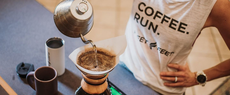 A woman pours coffee into a coffee machine.