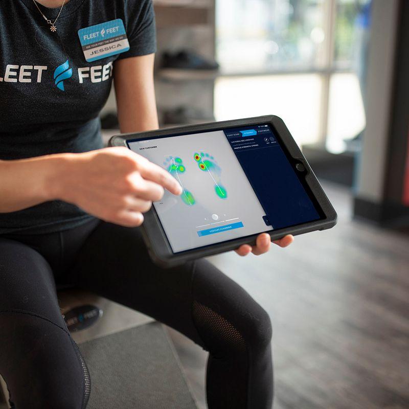 A Fleet Feet employee shows a customer her foot scan