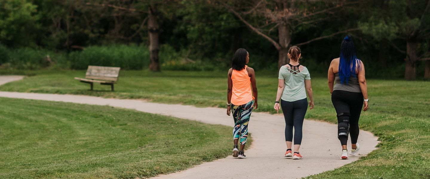 3 women walk together in a park