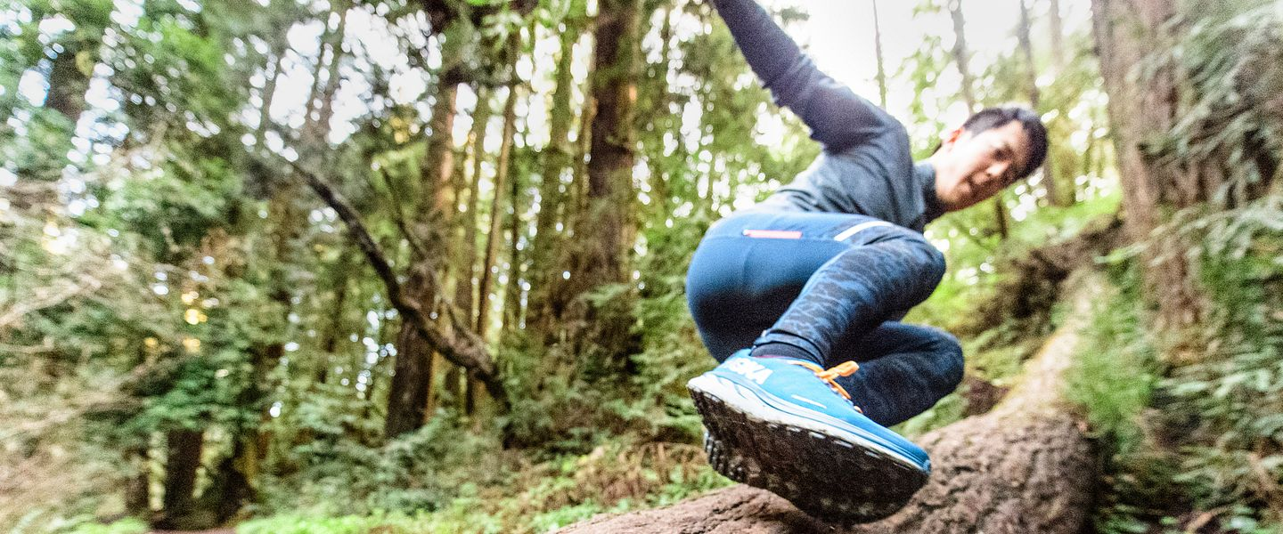 A runner jumps over a log in the woods