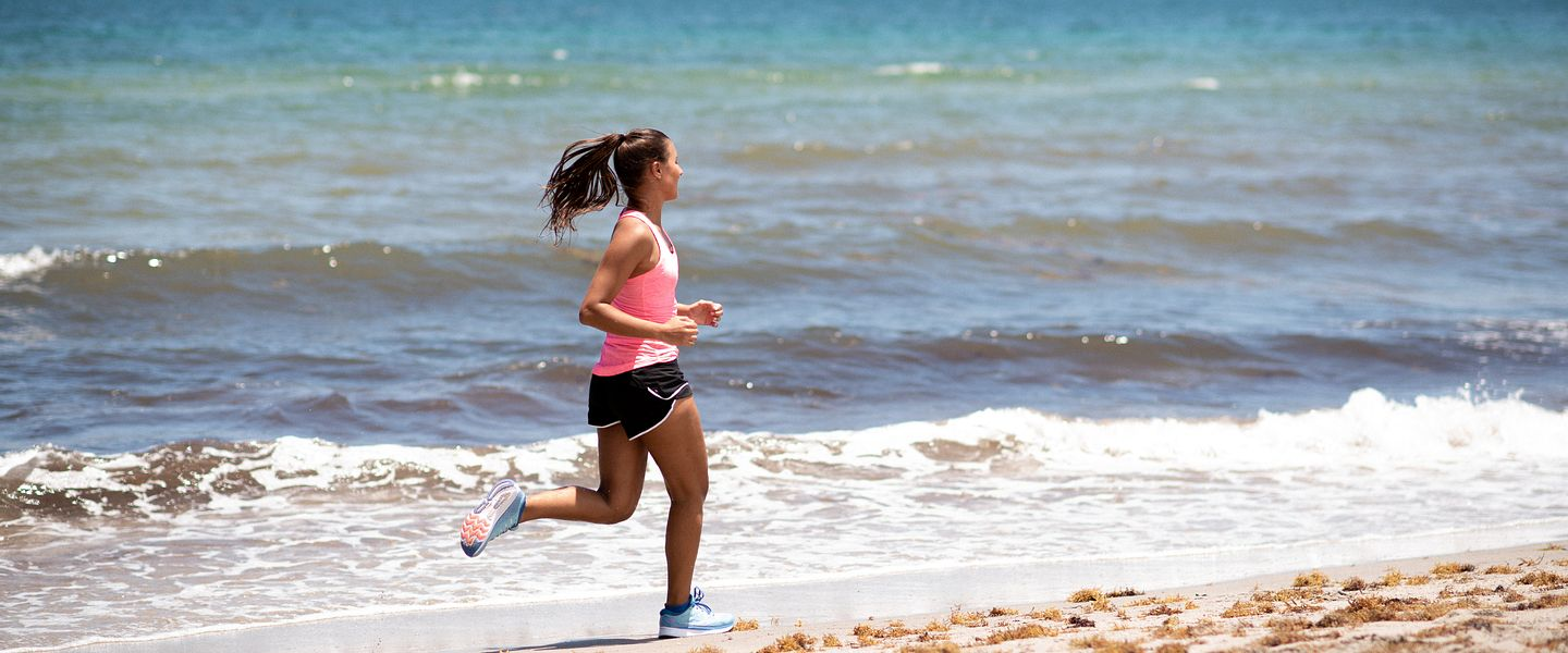 A woman runs alone on a beach in a pink New Balance top