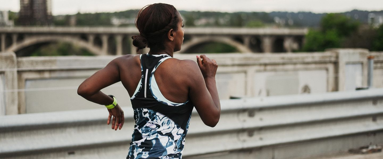 A woman races alone across a bridge