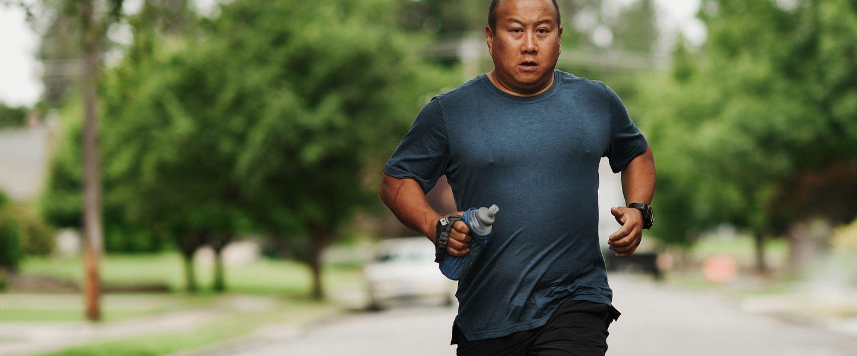 A man runs alone down a neighborhood street