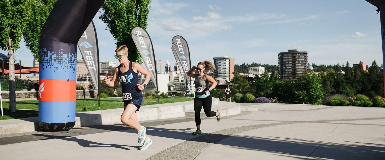 A women joyfully crosses a finish line at a race