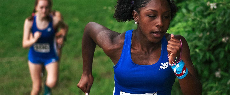 Two high school women race up a grass hill