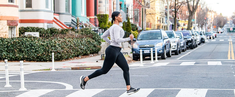 A woman on a run crosses the street