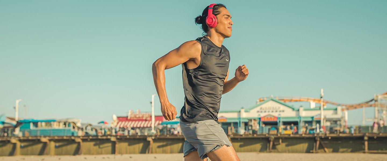 A man with headphones runs alone on a boardwalk
