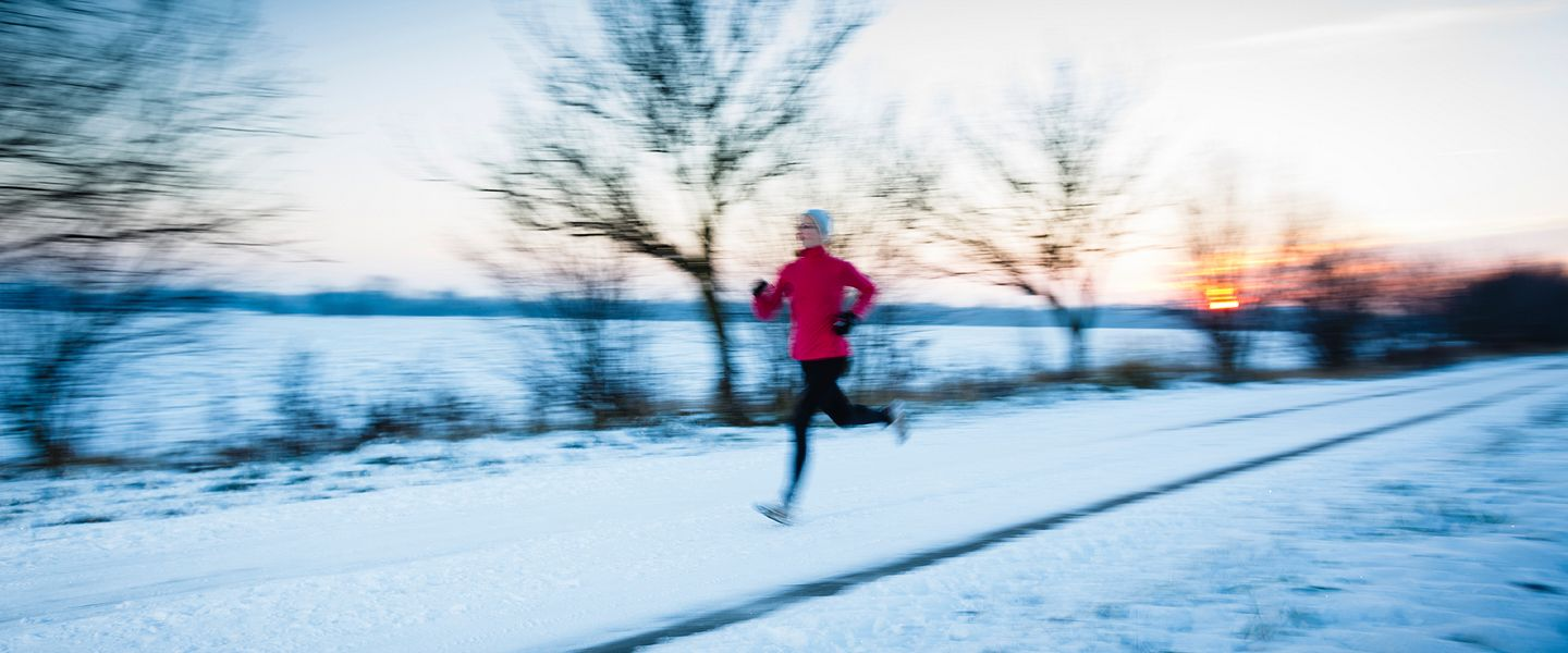 A runner training in the snow during winter